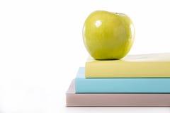Buch und grüner Apfel Stockbild