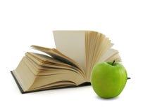 Buch und grüner Apfel Stockfotografie