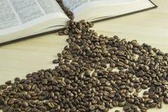 Buch und Kaffeebohnen auf einem Holztisch Stockfoto