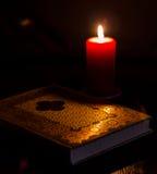 Buch und Kerze auf einer Tabelle Stockfotos