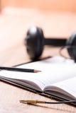 Buch und Kopfhörer auf hölzerner Tabelle, Musikidee Lizenzfreie Stockfotografie
