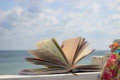 Buch und Schal im Strand Stockfotos