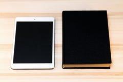 Buch und Tablette auf dem Tisch Stockfotografie