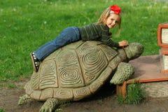 Bucha, Ucrania - 6 de mayo de 2018: Reserve el festival en el parque público, niña pequeña que miente en una tortuga gigante que  Foto de archivo libre de regalías