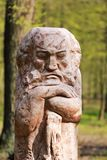 Wooden carved statue of a fairy tale mythical character, park landscape decoration against greenery blurred background. Bucha, Ukraine - April 25, 2017: Wooden Stock Images