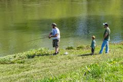 Leaning to Fish. Buchanan, VA – April 28th: Little learning how to fish on the James River from his father and uncle on a beautiful spring day. Buchanan stock image