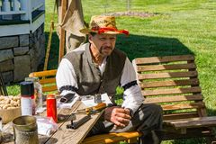 A Male Reenactor With a Hat Relaxing at the Confederate Encampment. Buchanan, VA - April 28th; A male reenactor with straw hat relaxing at the Confederate Royalty Free Stock Images