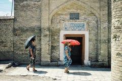 Buchara/Uzbekistan - 5 maggio 2010: donna che cammina davanti ad una casa tradizionale del bagno nella città murata storica del r fotografia stock
