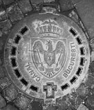 Bucharest City Sewer - Romania emblem grey. A manhole that says `CANAL BUCURESTI` on a cobblestone street in Bucharest Romania. Metal door contains also the Stock Image