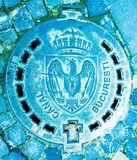 Bucharest City Sewer - Romania emblem. A manhole that says `CANAL BUCURESTI` on a cobblestone street in Bucharest Romania. Metal door contains also the eagle Stock Photo