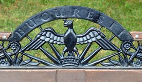 Bucharest Coat of Arms on park bench in Herastrau, Bucharest, Romania. An heraldic bird, part of the citys coat of arms in wrought iron atop a bench in Herastrau royalty free stock photography