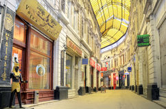 Bucharest - glass covered street. Macca-Vilacrosse passage is a fork-shaped, yellow glass covered street in central Bucharest, Romania. Built in 1891 it hosted Stock Photo