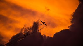 Bucharest international air show BIAS, air glider duo aerobatic team silhouette. In to the red sunset Stock Photos