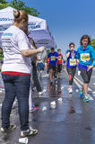 Runner take a water in a marathon race Stock Image