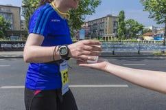 Runner take a water in a marathon race Stock Photos