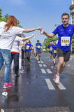 Marathon runner picking up water at service point Stock Photo
