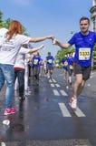 Marathon runner picking up water at service point Stock Photo