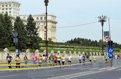 Bucharest internationell maraton: Löpare passerar den rumänska Parlen Royaltyfri Foto