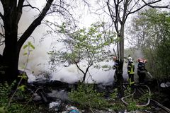Firefighters using water hoses to extinguish a fire. BUCHAREST, ROMANIA - APRIL 17: Firefighters try to extinguish with water a fire that spread across an Stock Images