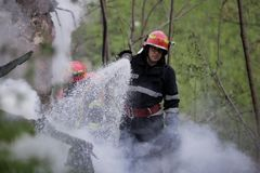 Firefighters using water hoses to extinguish a fire. BUCHAREST, ROMANIA - APRIL 17: Firefighters try to extinguish with water a fire that spread across an Stock Photography