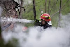 Firefighters using water hoses to extinguish a fire. BUCHAREST, ROMANIA - APRIL 17: Firefighters try to extinguish with water a fire that spread across an Stock Photos