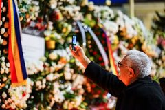 In memoriam of death of King Mihai of Romania. BUCHAREST, ROMANIA - 15 DECEMBER 2017: People gathered to bring flowers as the last homage in memory of King Mihai stock photography