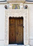 Bucharest, Romania: carved wooden door under mosaic. Elaborately carved wooden door at the Romanian Patriarchate, Bucharest, Romania. The Patriarchate is the royalty free stock images