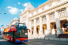 City tour bus and National Museum of Romanian History on Victory street in Bucharest, Romania