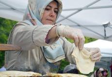 bucharest romania Maj 22, 2016 Den turkiska kvinnan supervizes den stekheta processen av ett traditionellt plant bröd på en sajug Arkivfoton