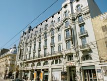 Boulevard Queen Elisabeta in Bucharest Romania with people and c. BUCHAREST, ROMANIA - MAR 31 2016: Spanish Instituto Cervantes housed in iconic Hotel Cismigiu royalty free stock photos