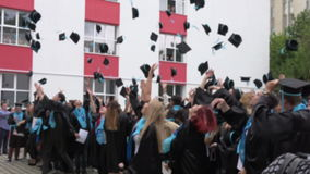 BUCHAREST,ROMANIA,MAY 2016.Blurred image of students throwing hats in the air,graduating High School Benjamin Franklin.
