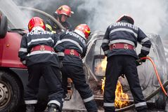 Firemen team dismantle a car on fire. Bucharest, Romania - May 07, 2018: Cars on fire blow up on the streets of Bucharest Stock Photos