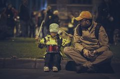 Protests against Rosia Montana gold mine, Bucharest, Romania. Bucharest, Romania - October 6, 2013: Father teaches his kid how to play the drum during the riot Royalty Free Stock Image