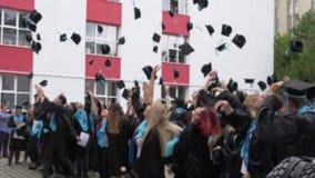 BUCHAREST RUMÄNIEN, MAJ 2016 Suddig bild av studenter som kastar hattar i luften som avlägger examen högstadiet Benjamin Franklin lager videofilmer