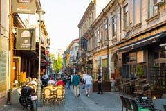 Bucharest Rumänien - 28 04 2018: Turister i gamla stad och restauranger på i stadens centrum Lipscani gata, en av mest Arkivbild