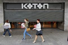 Bucharest street photography - Unirii Square - Koton shop. Bucharest, Romania - May 16, 2018: A few pedestrians pass in front of the Koton store, before opening Royalty Free Stock Photos