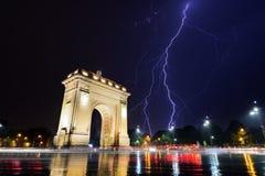 Bucharest Triumph båge i den ljusa stormen vid natt Fotografering för Bildbyråer