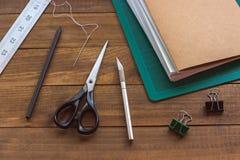 Buchbindereiwerkzeuge auf Holztisch stockbild