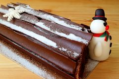 Buche de Noel or Chocolate Yule Log Cake for Christmas Celebration with a Cute Snowman Marzipan on a Wooden Table stock photos