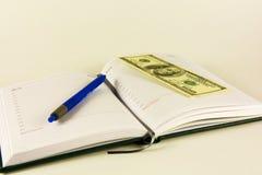 Buchen Sie für Aufzeichnungen, Stift und Banknoten 100 Dollar Lizenzfreie Stockfotografie