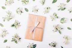 Buchen Sie im Packpapier mit Band unter grünen Blumen und verlassen Sie Stockfotografie