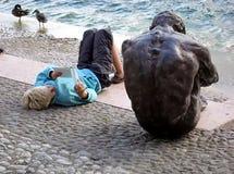Buchen Sie Lesung auf einem See nahe einer männlichen traurigen Bronzestatue Stockbild