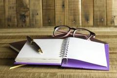 Buchen Sie mit Gläsern und Stift auf dem hölzernen Hintergrund Stockfotografie