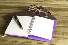Buchen Sie mit Gläsern und Stift auf dem hölzernen Hintergrund Stockfoto