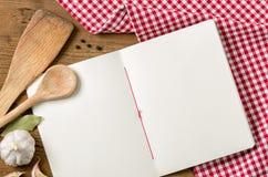 Buchen Sie mit hölzernen Löffeln auf einer roten karierten Tischdecke Lizenzfreie Stockfotos