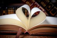 Buchen Sie Seite in der Herzform mit Bibliothekshintergrund Stockfoto