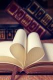 Buchen Sie Seite in der Herzform mit Bibliothekshintergrund Lizenzfreies Stockbild