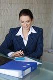 Buchhalter, der im Büro mit Zahnlächeln berechnet Lizenzfreie Stockbilder