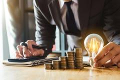 Buchhalter, der an Schreibtisch im Büro unter Verwendung des Taschenrechners und des Smartphone arbeitet, um Budget zu berechnen stockfoto