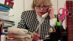 Buchhaltungsleiter der älteren Frau in den Gläsern und mit Telefon stock video